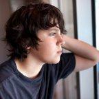 Un enfant regardant par la fenêtre, l'air pensif